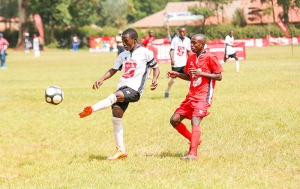Ismael Mohammed (in white), from Kinondo school, makes a pass to goal, as, Salim Badi, from St. Anthony school, eyes for the ball.