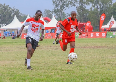 Bill Clinton of Agoro Sare boys (L) runs with the ball past  Abdiraham Dajib of Boys Town in the the Copa Coca cola under boys 16 National Finals Tournament 2019 at Kisumu National Polytechnic Kisumu.